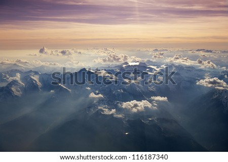 High altitude view of sunset over the mountains. Rays of light shine through the hazy atmosphere. - stock photo
