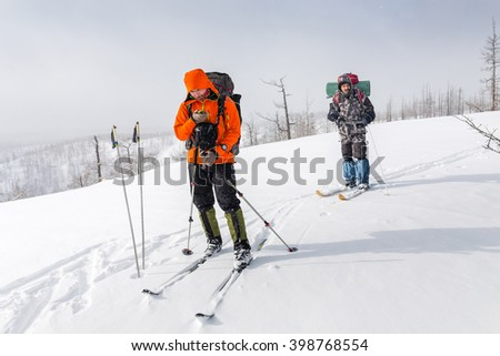 High altitude view of two skiers walking on a mountain ridge in the Ural mountains. One hiker looking in navigator map - stock photo