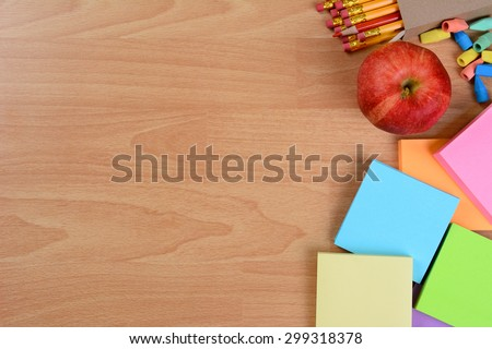 High angle back to school still life on top of a wood teachers desk. An apple, note pads, pencils and erasers with copy space. - stock photo