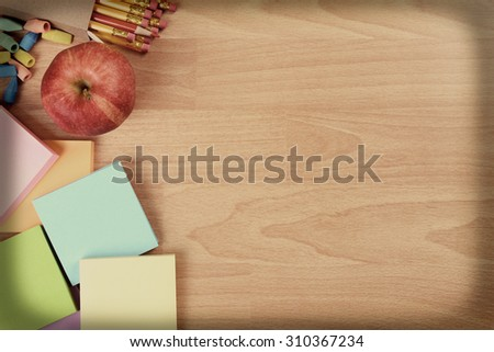 High angle back to school still life on top of a wood teachers desk with a vintage instagram look. An apple, note pads, pencils and erasers with copy space. Intentional vignette applied. - stock photo