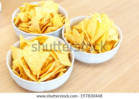 High-angle close-up of three white round porcelain bowls full of salty nachos, Mexican dish of tortilla chips, on wooden table - stock photo