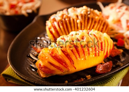 High Angle Close Up Still Life of Sliced Baked Potatoes Garnished with Sliced Salami Meat and Melted Cheese Served on Hot Cast Iron Pan and Surrounded by Fresh Ingredients on Rustic Wooden Table - stock photo