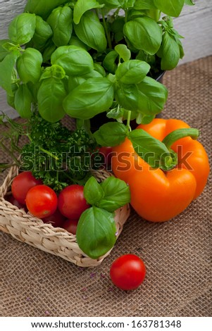 High angle close up view of a colourful rustic arrangement of farm fresh basil, bell peppers, tomato and parsley to be used as cooking ingredients - stock photo