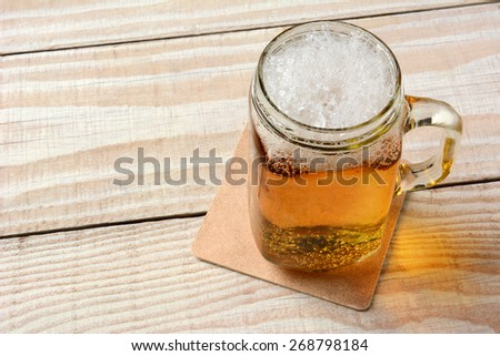 High angle closeup of a mason jar full of beer on a rustic wood table. - stock photo