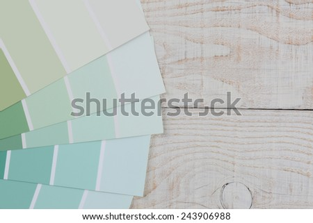 High angle closeup of green paint chip samples fanned out on a rustic white wood table. Horizontal format with copy space.  - stock photo