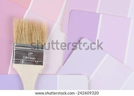 High angle closeup shot of a paint brush laying on a color paint chip samples. Horizontal format. - stock photo