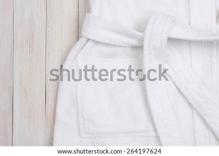 High angle closeup shot of a white terry cloth bathrobe on a rustic white wood surface. Horizontal format with copy space.  - stock photo