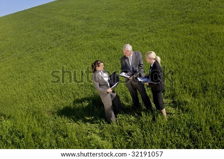 High angle concept shot of a team of three people one man and two women in a green field with a bright blue sky discussing plans. Shot on location.