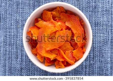 High angle directly above bowl full of thin sliced dehydrated papaya on blue fabric placemat - stock photo