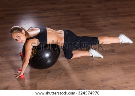 High Angle Full Length View of Young Woman Looking Up at Camera and Performing Leg Lift Core Strengthening Exercises Using Inflatable Exercise Ball and Hand Weights in Studio with Hardwood Floors