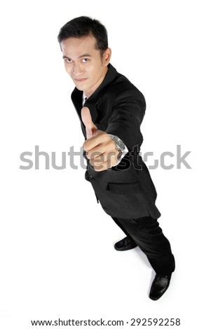 High angle full shot of young Asian businessman giving a thumb up to camera, isolated on white background - stock photo