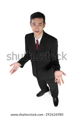 High angle full shot of young Asian businessman looking at camera with quizzical expression, isolated on white background - stock photo