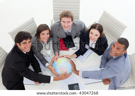 High angle of a diverse business team holding a terrestrial globe in the office