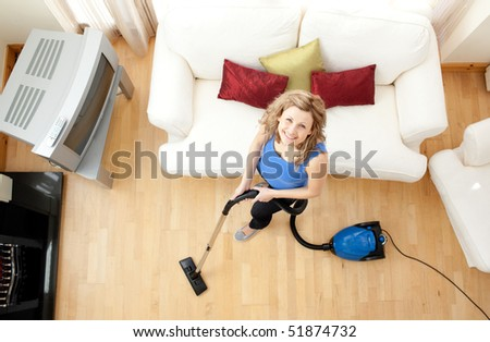 High angle of a mirthful woman vacuuming in the living-room - stock photo
