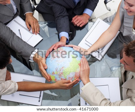 High angle of business team holding a terrestrial globe. Global expansion - stock photo