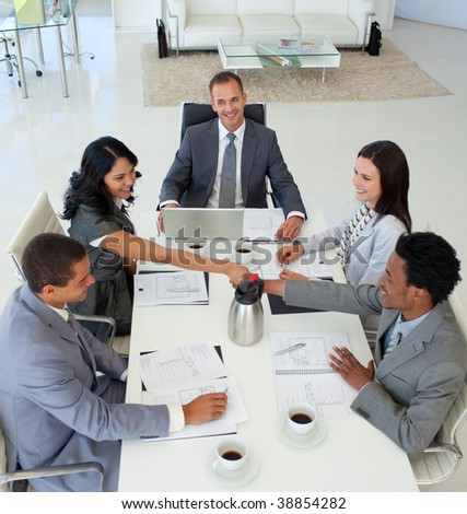 High angle of businesswoman and businessman shaking hands in a meeting - stock photo