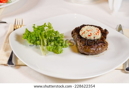 High Angle of Steak with Herbed Butter and Garnish Served on Plate in Restaurant