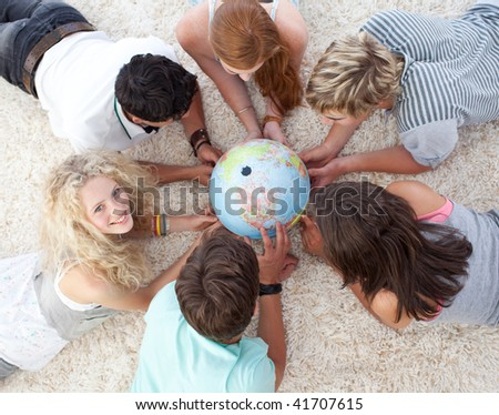 High angle of teenagers lying on the floor examining a terrestrial world - stock photo