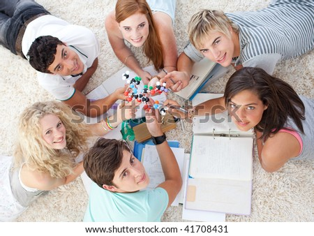 High angle of teenagers studying Science on the floor in a house - stock photo