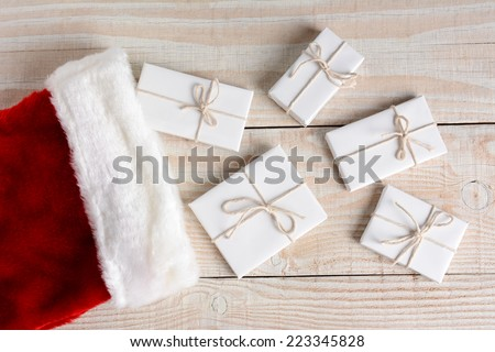 High angle photo of five Christmas presents wrapped in white paper and tied with white string and a stocking. The gifts are on a whitewashed wood table. Horizontal format. - stock photo