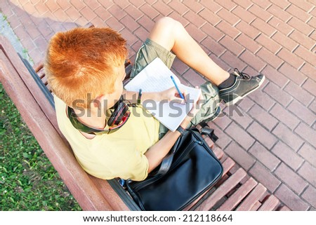 High angle portrait of a left-handed teen boy (schoolboy). Teenager is sitting and writing on the bench. Young red-head boy is studying. Caucasian male model (14 year). Sunny day. Education concept.