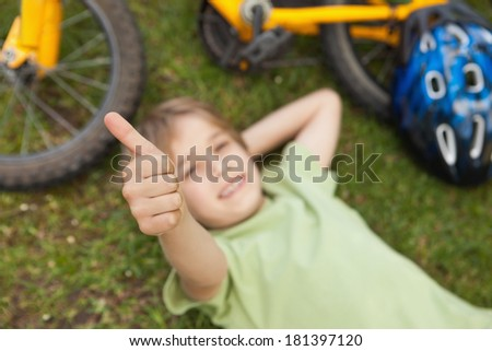 High angle portrait of a relaxed boy gesturing thumbs up at the park - stock photo