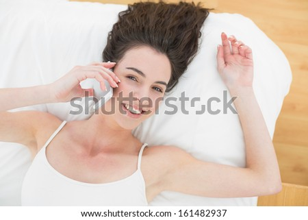 High angle portrait of a relaxed young woman using mobile phone in bed at home