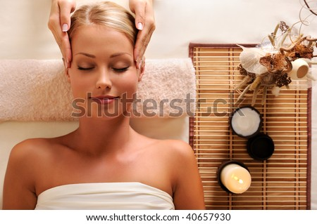 High angle portrait of an attractive female getting recreation massage of head - stock photo