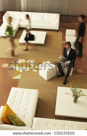 High angle portrait of businessman holding newspaper with coworkers walking in office - stock photo