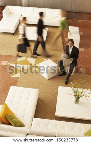 High angle portrait of businessman holding newspaper with coworkers walking in office lobby - stock photo
