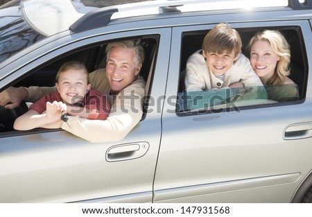 High angle portrait of cheerful girl showing car keys while sitting with family in car - stock photo