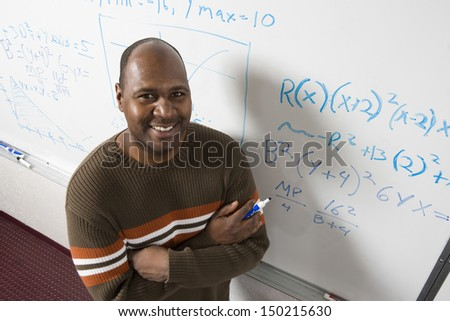 High angle portrait of confident teacher solving math's equations on whiteboard in classroom - stock photo