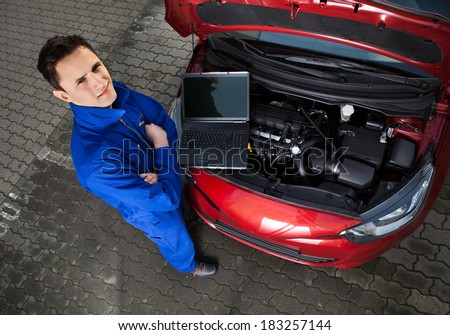 High angle portrait of confident young mechanic with arms crossed standing by car on street - stock photo