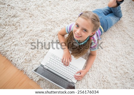 High angle portrait of cute girl using laptop while lying on rug in living room - stock photo