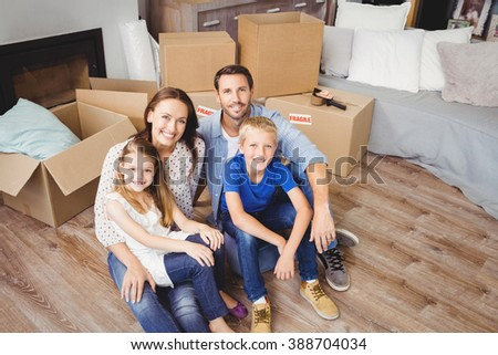 High angle portrait of family with cardboard boxes at home - stock photo