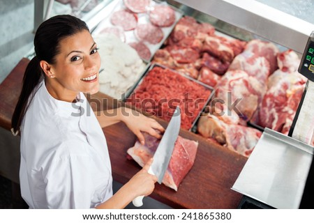 High angle portrait of happy female butcher cutting meat at butchery counter - stock photo