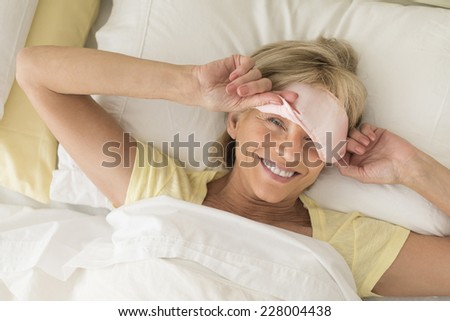 High angle portrait of happy mature woman wearing sleep mask while lying on bed - stock photo