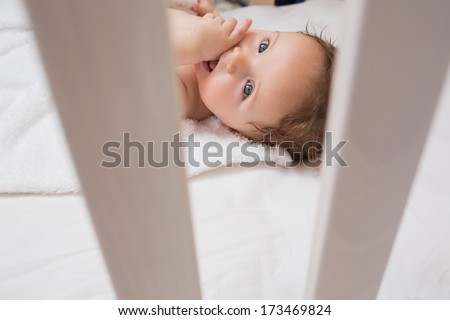 High angle portrait of lovely baby with finger in mouth lying on crib - stock photo
