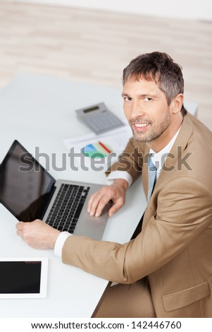 High angle portrait of mature businessman with laptop and digital tablet at desk in office - stock photo