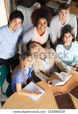 High angle portrait of mature teacher and students with books smiling together at desk in classroom - stock photo
