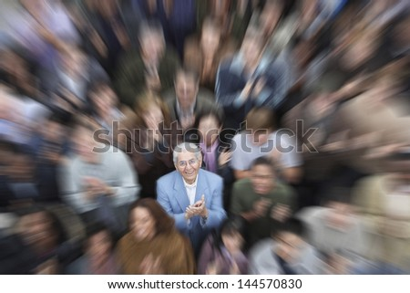 High angle portrait of senior man with crowd applauding - stock photo