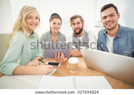 High angle portrait of smiling business people while sitting at desk