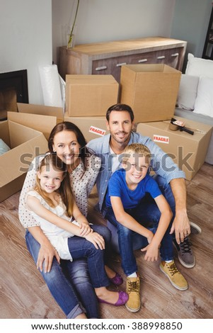 High angle portrait of smiling family with cardboard boxes at home - stock photo