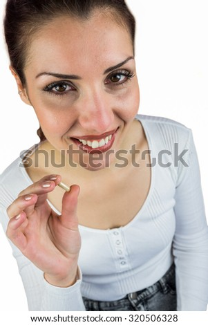 High angle portrait of smiling woman holding pill against white background - stock photo