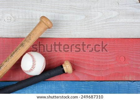 High angle shot of a baseball and bats on a red, white and blue picnic table. Horizontal format with copy space. Suitable for American Holidays: 4th of July and Memorial Day, - stock photo