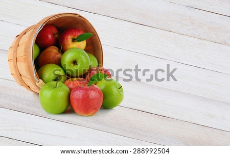 High angle shot of a basket full of Gala and Granny Smith apples spilling out onto a rustic wood surface. - stock photo