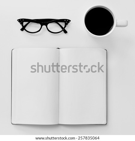 high-angle shot of a blank notebook, a pair of black plastic-rimmed eyeglasses for women and a cup of coffee on a white table - stock photo