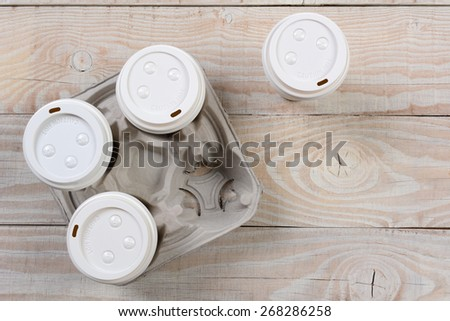 High angle shot of a cardboard take out coffee carrier on a white wood rustic table.Horizontal format with copy space. - stock photo