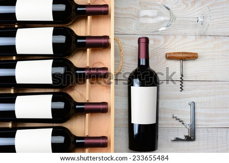 High angle shot of a case of red wine bottles with blank labels next to a single bottle a wineglass and cork screws on a rustic white wood table. Horizontal format. - stock photo