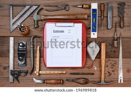 High angle shot of a contractors estimate form surrounded by his well used tools. Horizontal format on a rustic wood background. - stock photo